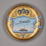 Ehrenteller. Abgebildet sind die Kontinente Europa und Amerika, das Flugzeug, ein Schiff und Freiherr von Hünefeld, Mayor Fritz und Hauptmann Kohl.